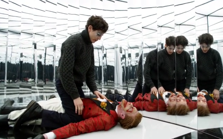 The mime straddling an unconscious Joker in the hall of mirrors.