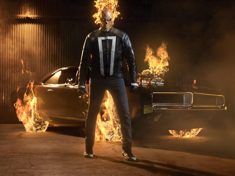 Ghost Rider with his skull on fire, standing in front of a car with the tires and engine on fire as well.