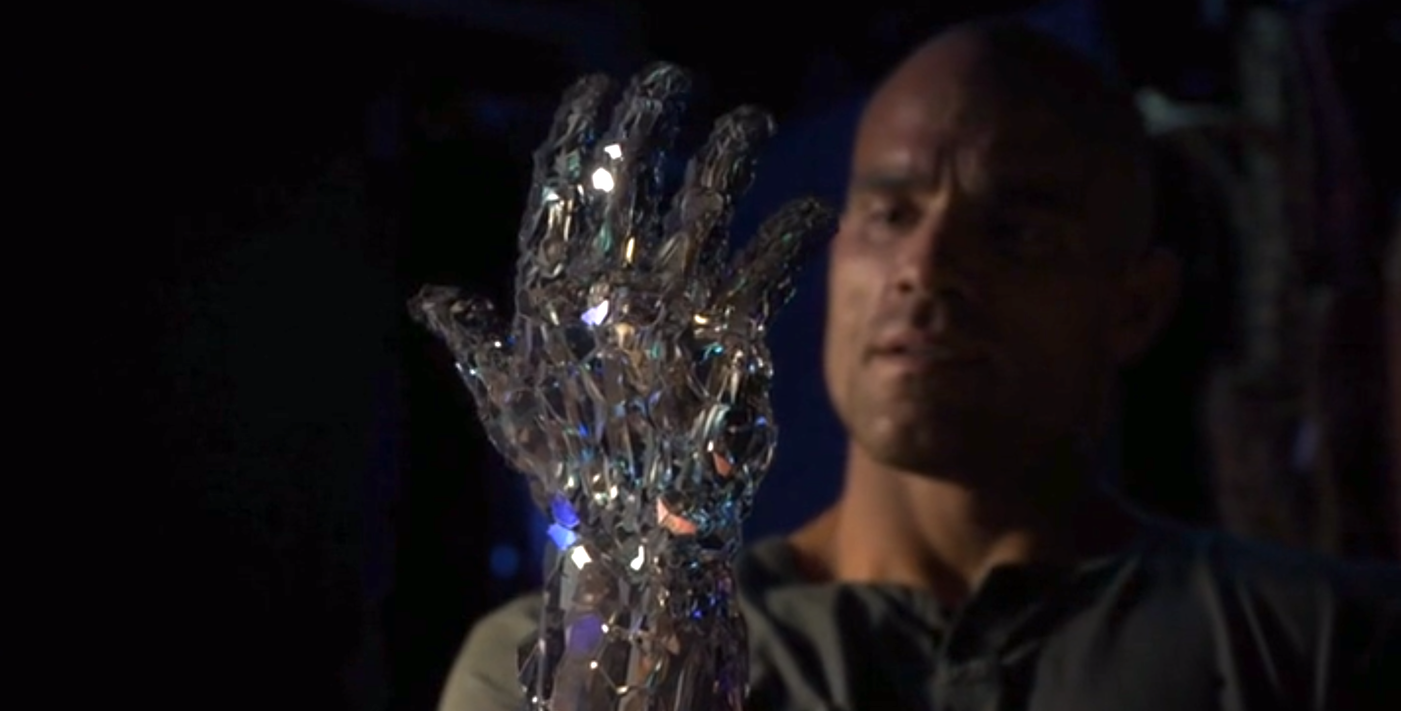 A man looking at his own hand which is becoming crystal.