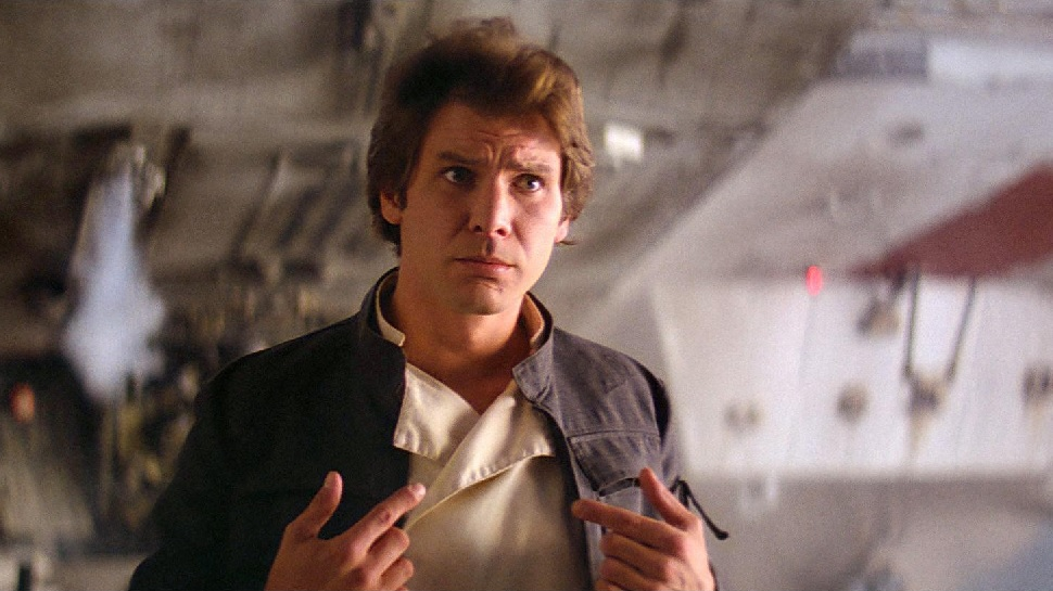 Harrison Ford as Han Solo standing in front of the Millenium Falcon.