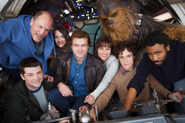 A picture of the cast and original directors of Solo: A Star Wars Story, in the cockpit of the Millenium Falcon.