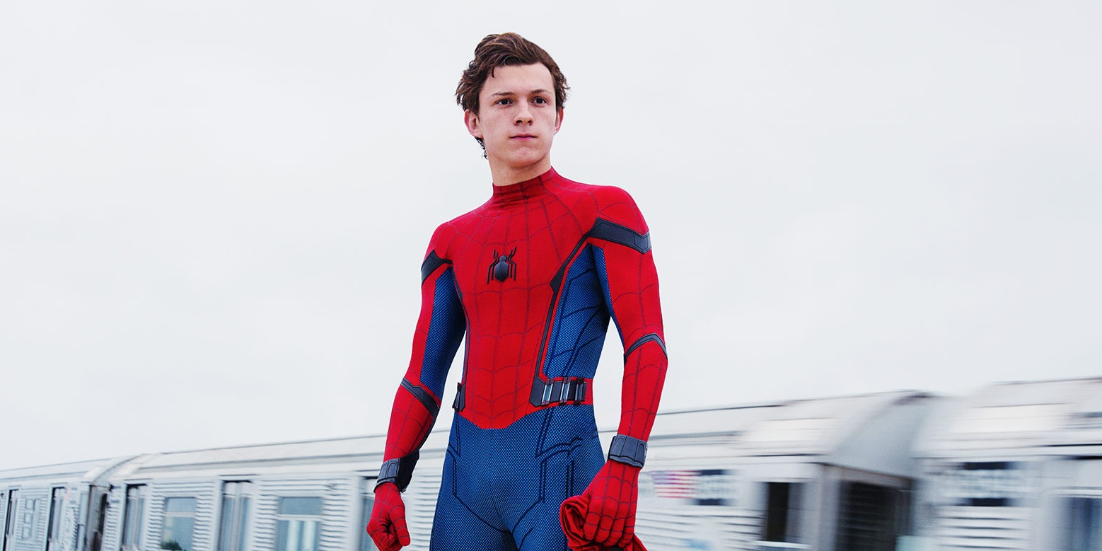 Tom Holland in Spider-Man costume, without his mask on, standing in front of a train.
